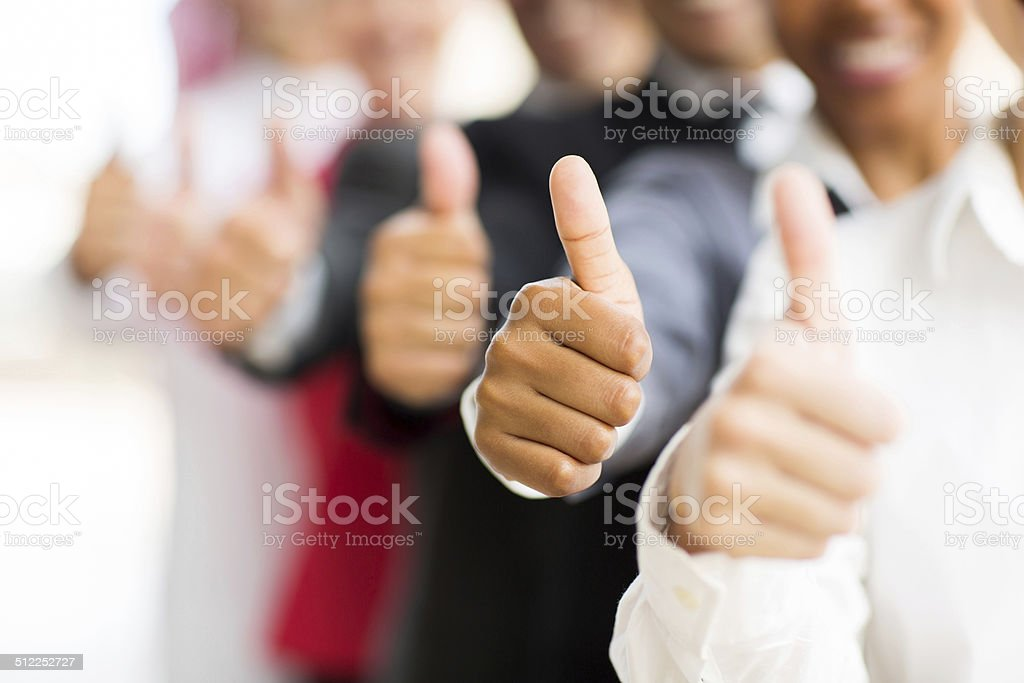 business people giving thumbs up stock photo