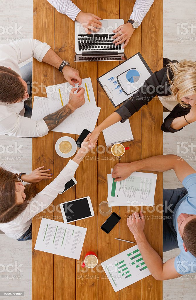 Agreement at business meeting. Busy people work in office, top view...