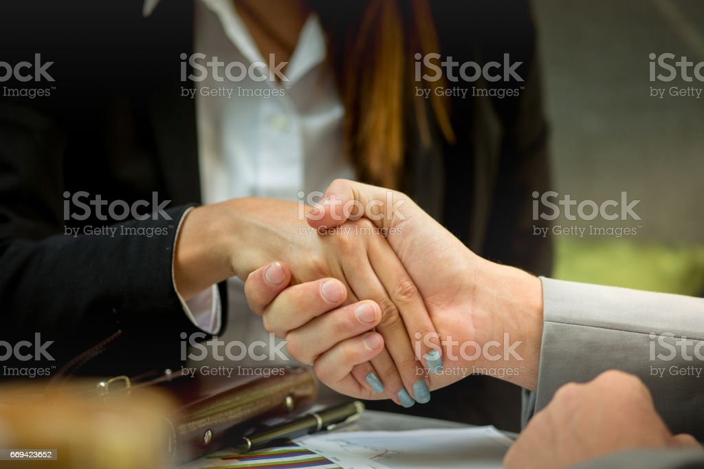 Business people handshaking demonstrating their agreement to sign...