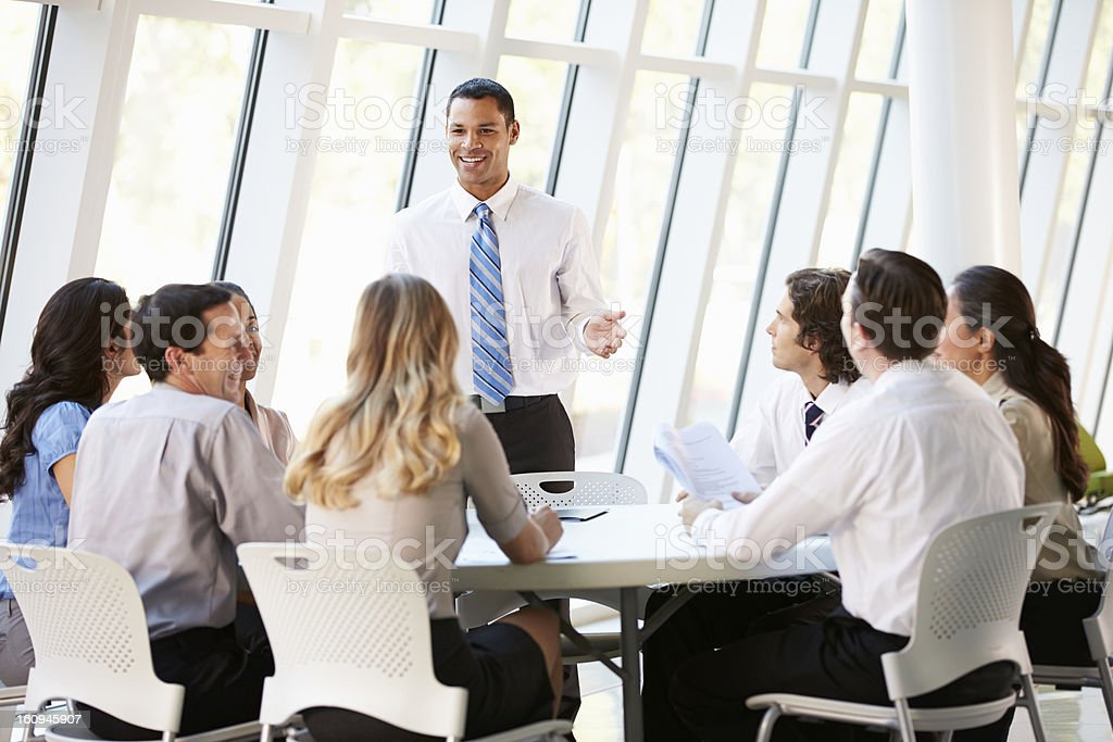 Business People Having Board Meeting In Modern Office Smiling