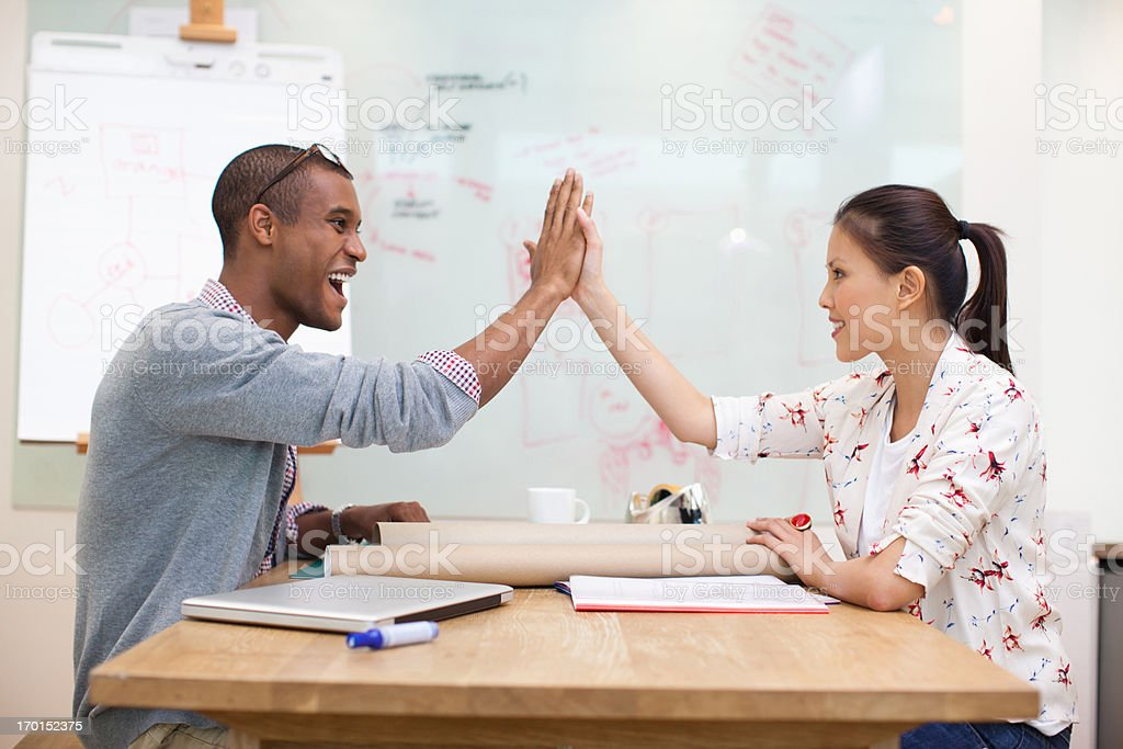 Business people high fiving in office royalty-free stock photo