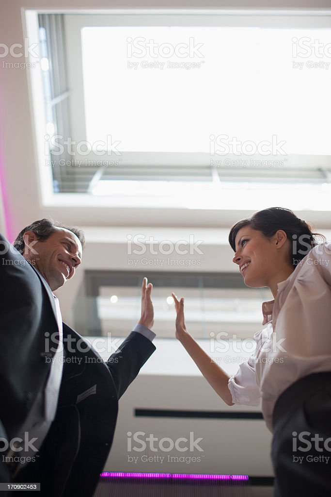 Business people high-fiving in office royalty-free stock photo