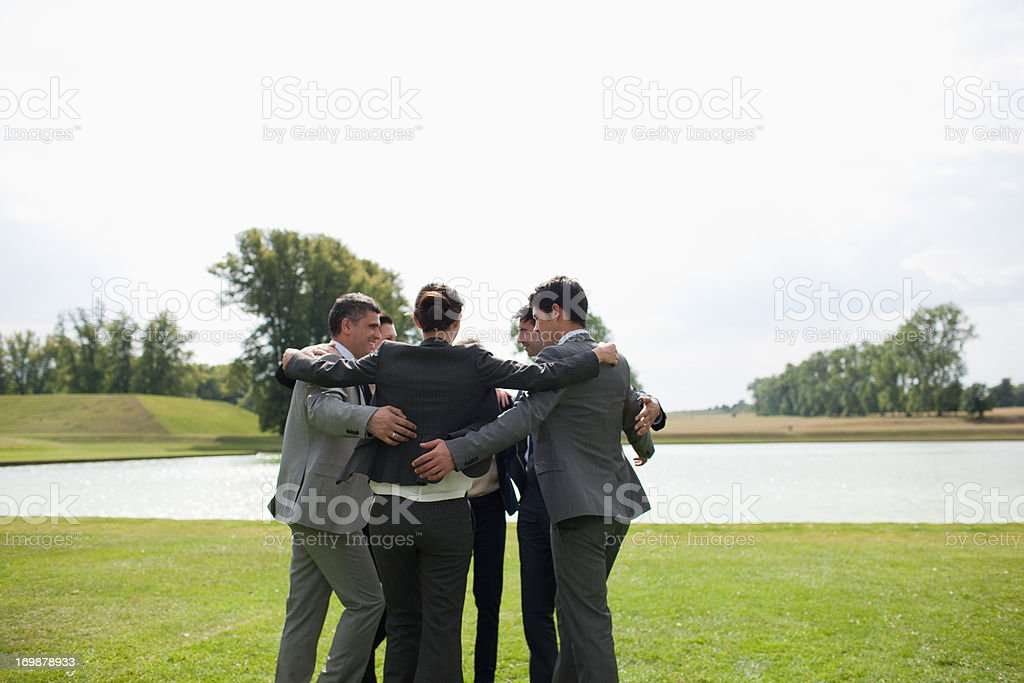 Business people holding hands in a circle outdoors stock photo