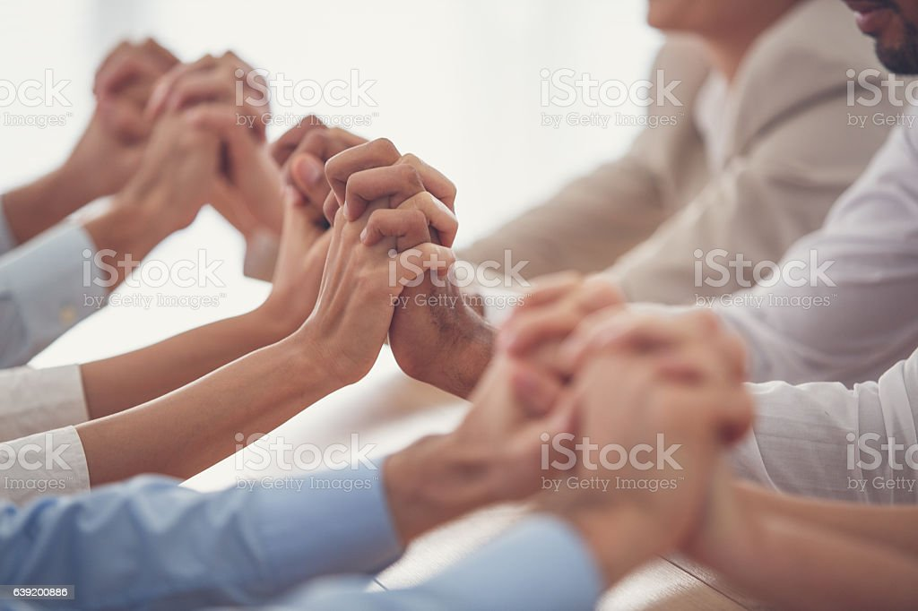 Business people holding hands, showing togetherness stock photo