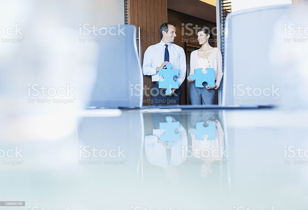 Business people holding jigsaw puzzle pieces in conference room royalty-free stock photo