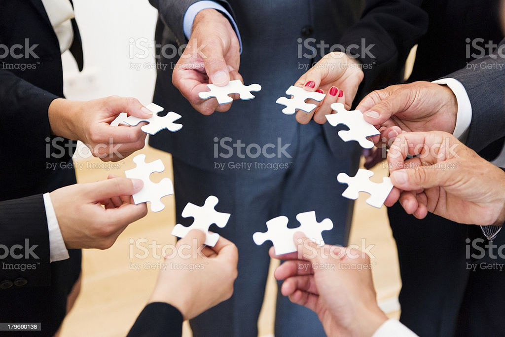 Business people holding jigsaw puzzle pieces royalty-free stock photo