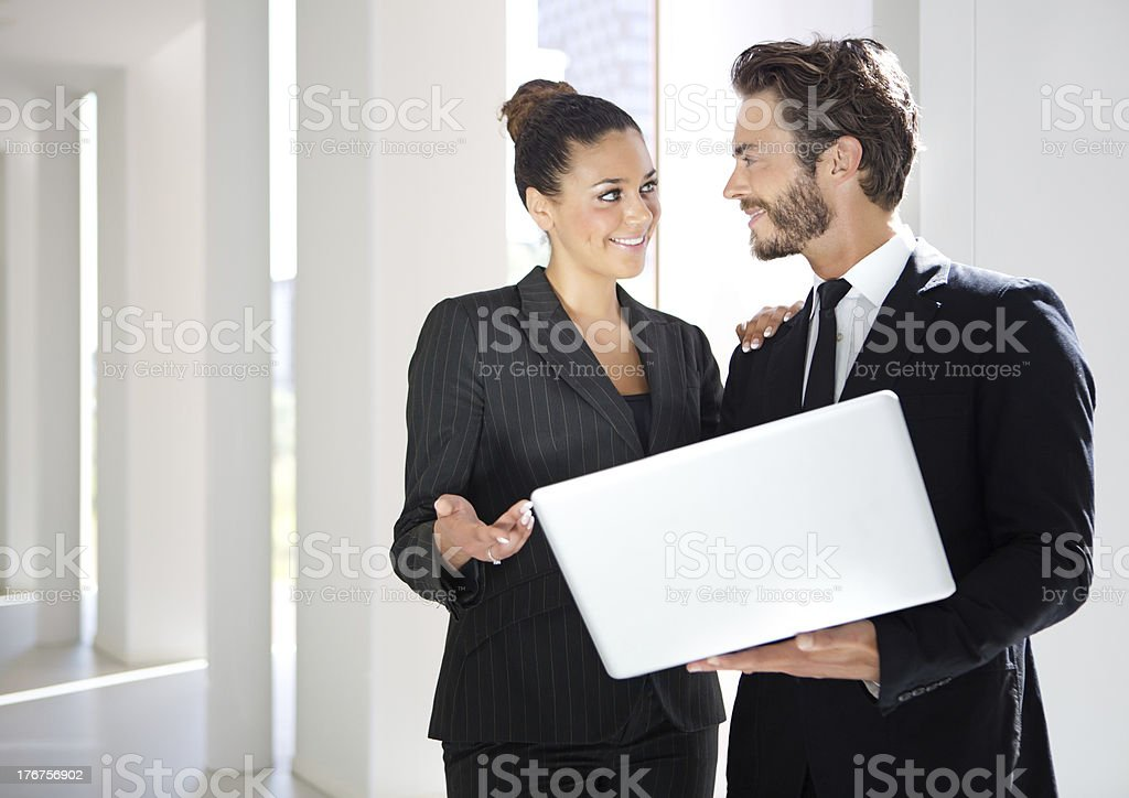 business people holding laptop, discussing, smiling royalty-free stock photo