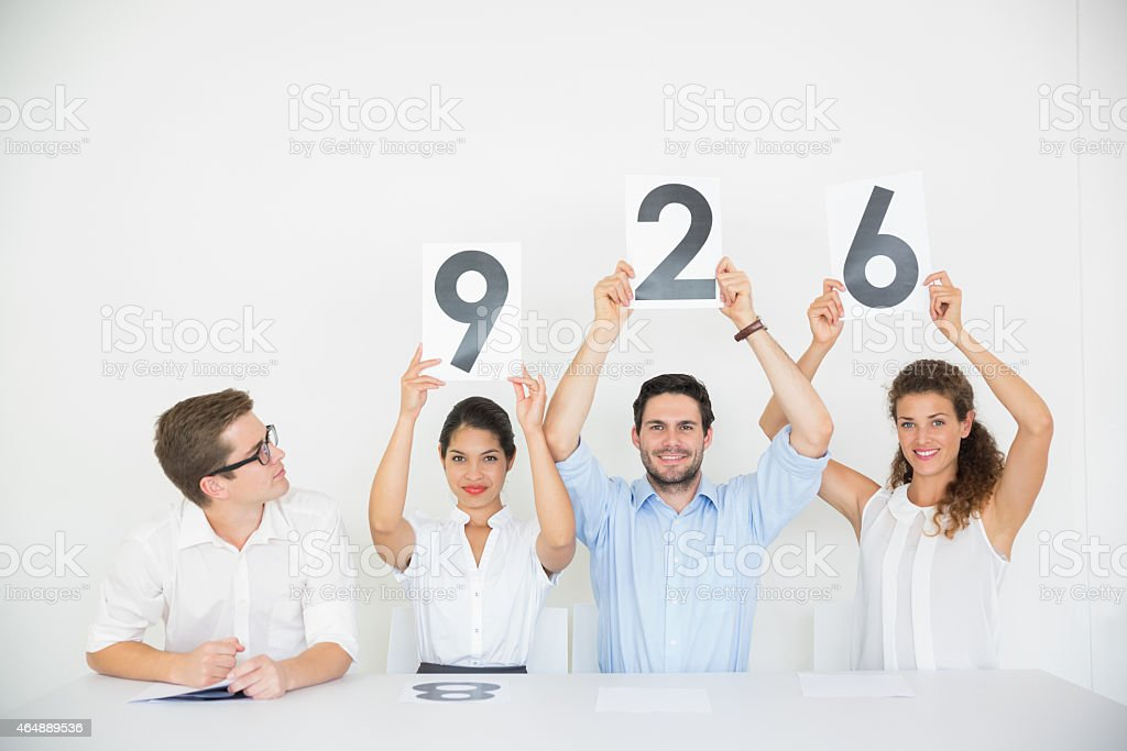 Business people holding score signs stock photo