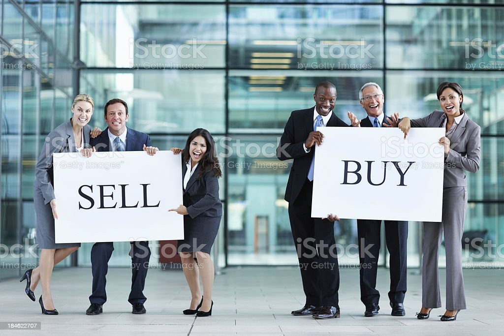 Business people holding up 'buy' and 'sell' boards royalty-free stock photo