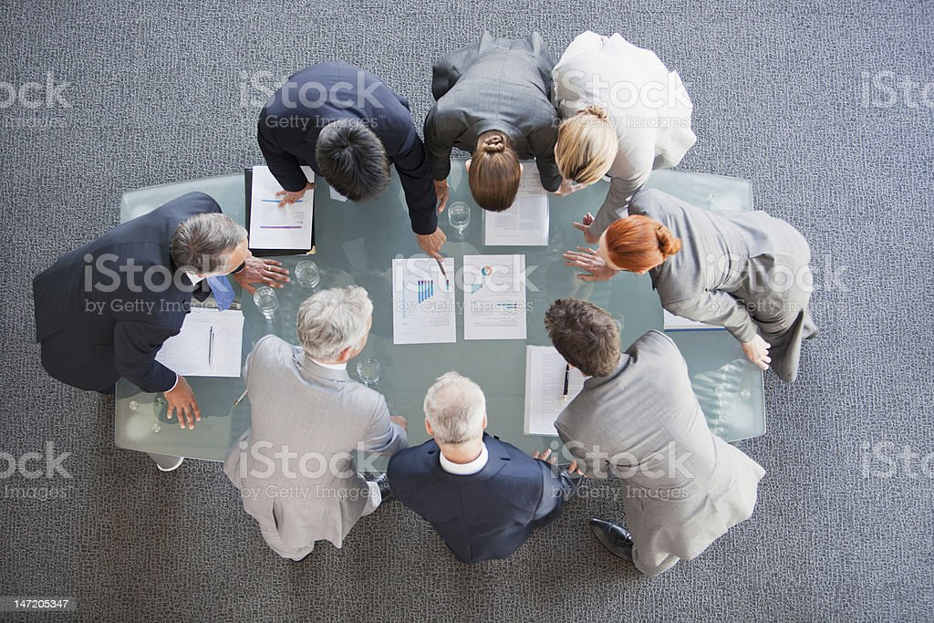 Business people huddled around paperwork on table stock photo