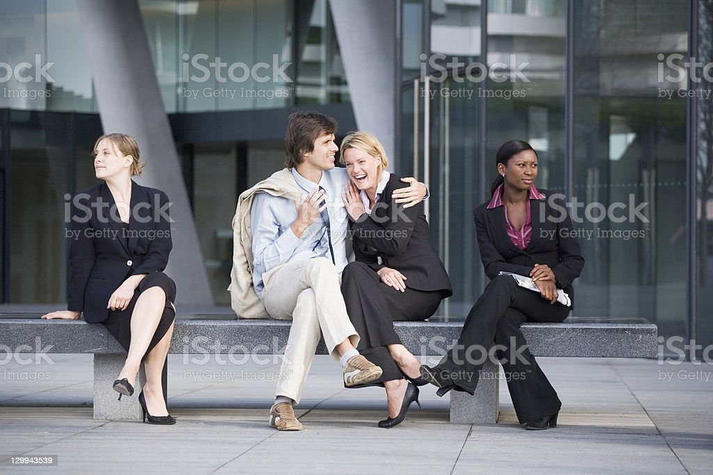 Business people ignoring couple on bench stock photo