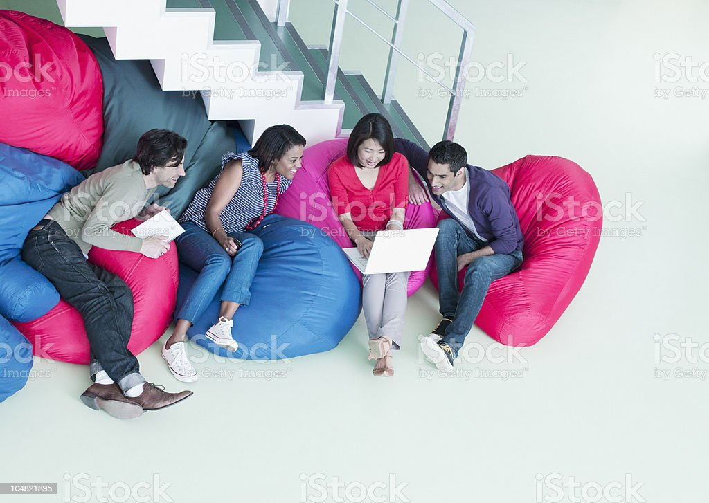 Business people in bean bag chairs looking at laptop stock photo