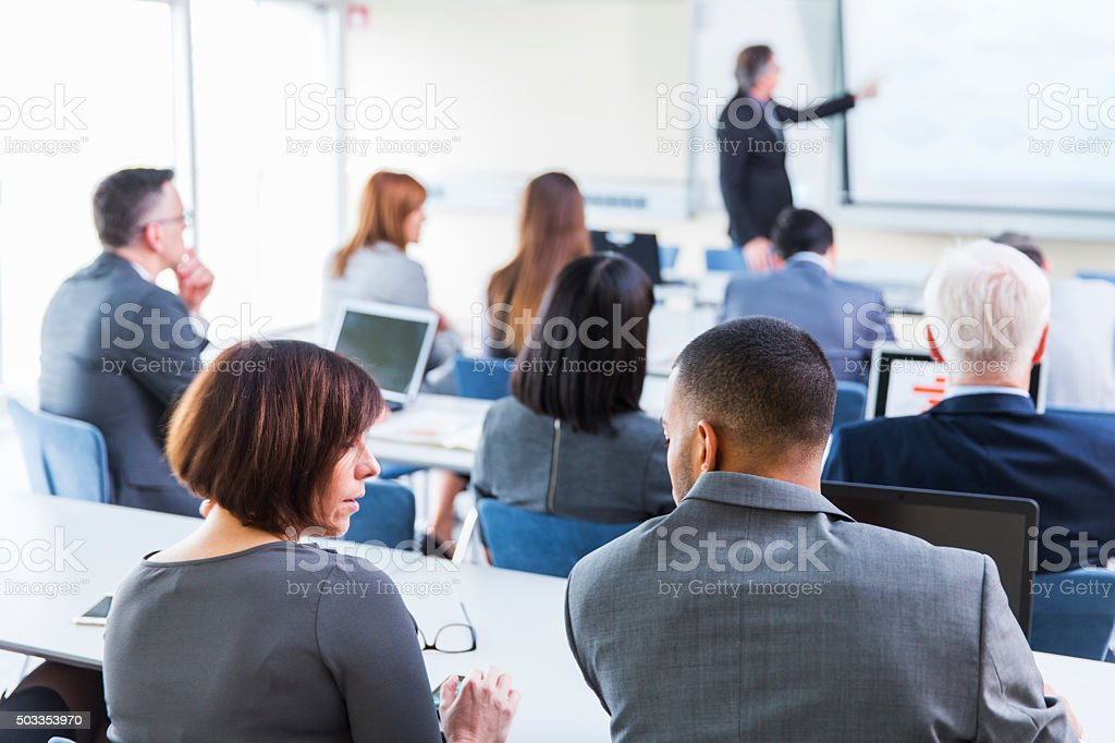 Business people in education room listening lecture of senior teacher stock photo