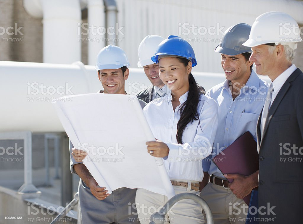 Business people in hard-hats reviewing blueprints outdoors stock photo