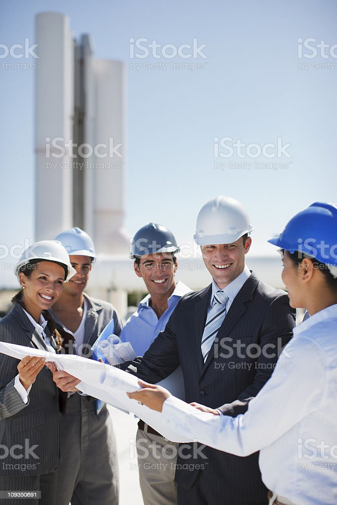 Business people in hard-hats reviewing blueprints outdoors royalty-free stock photo