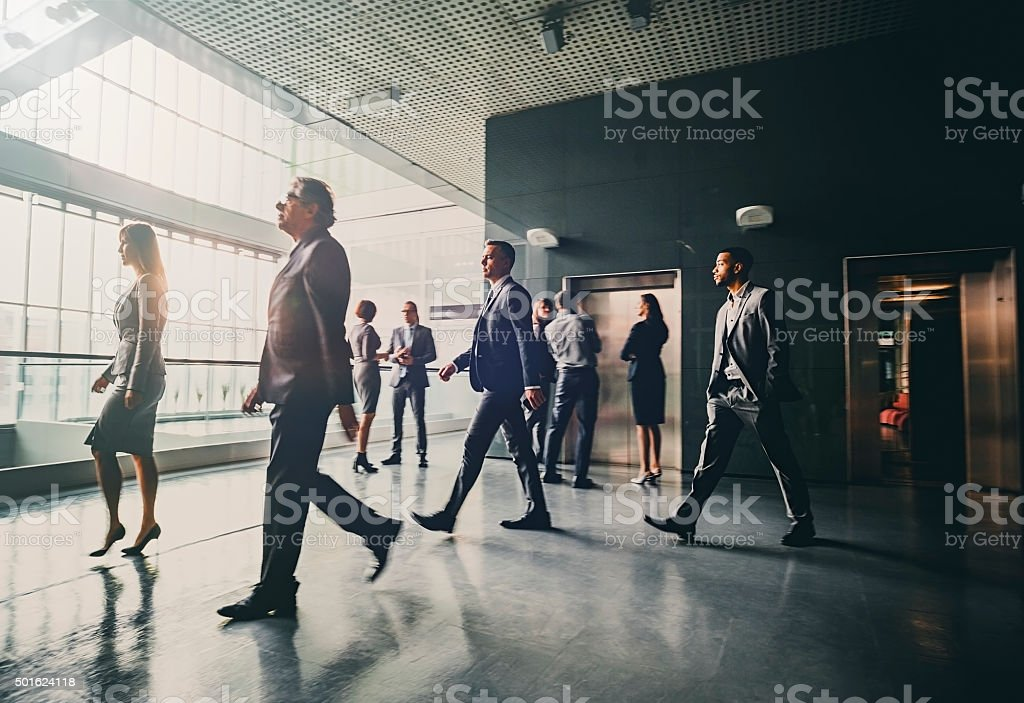 Business people in lobby walking stock photo