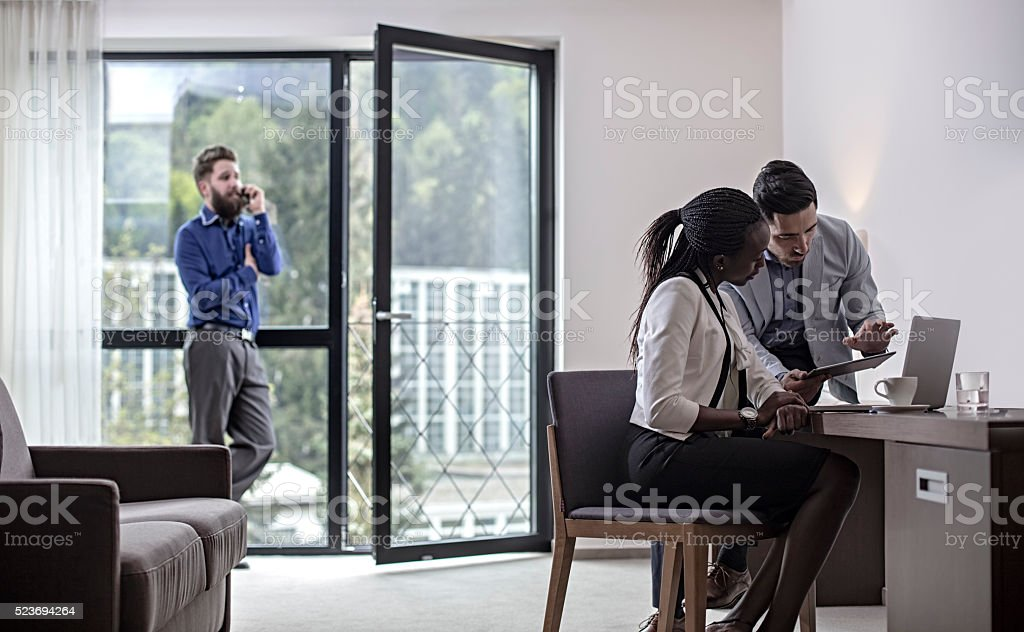 Business people in meeting in hotel room suite stock photo