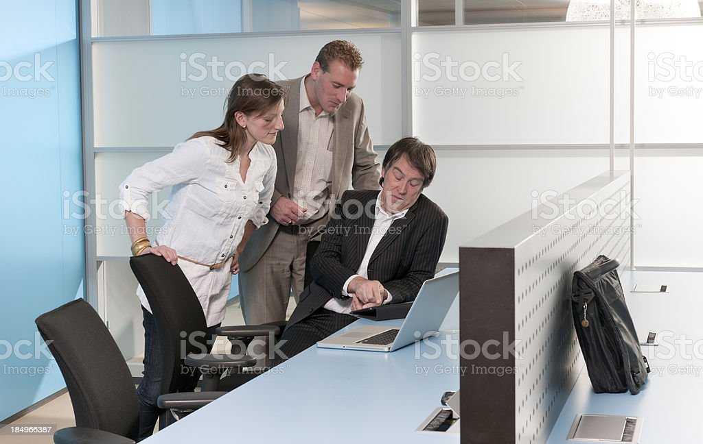 business people in office looking at laptop stock photo