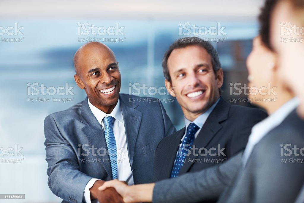 Business people in suits shaking hands and smiling royalty-free stock photo