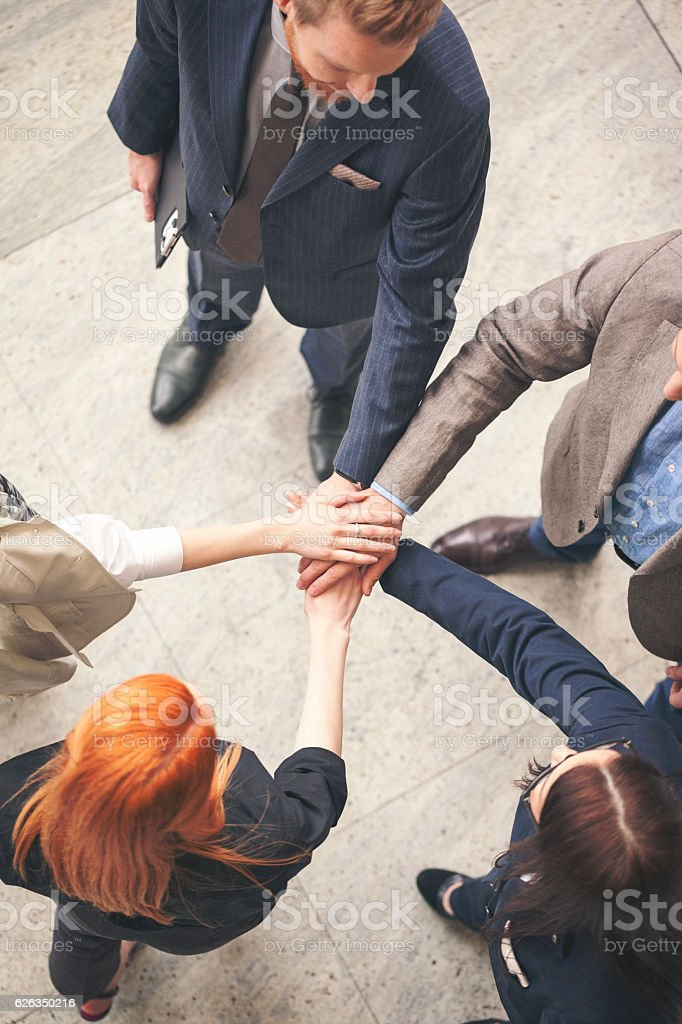 Business people in the lobby joining hands overhead shot stock photo