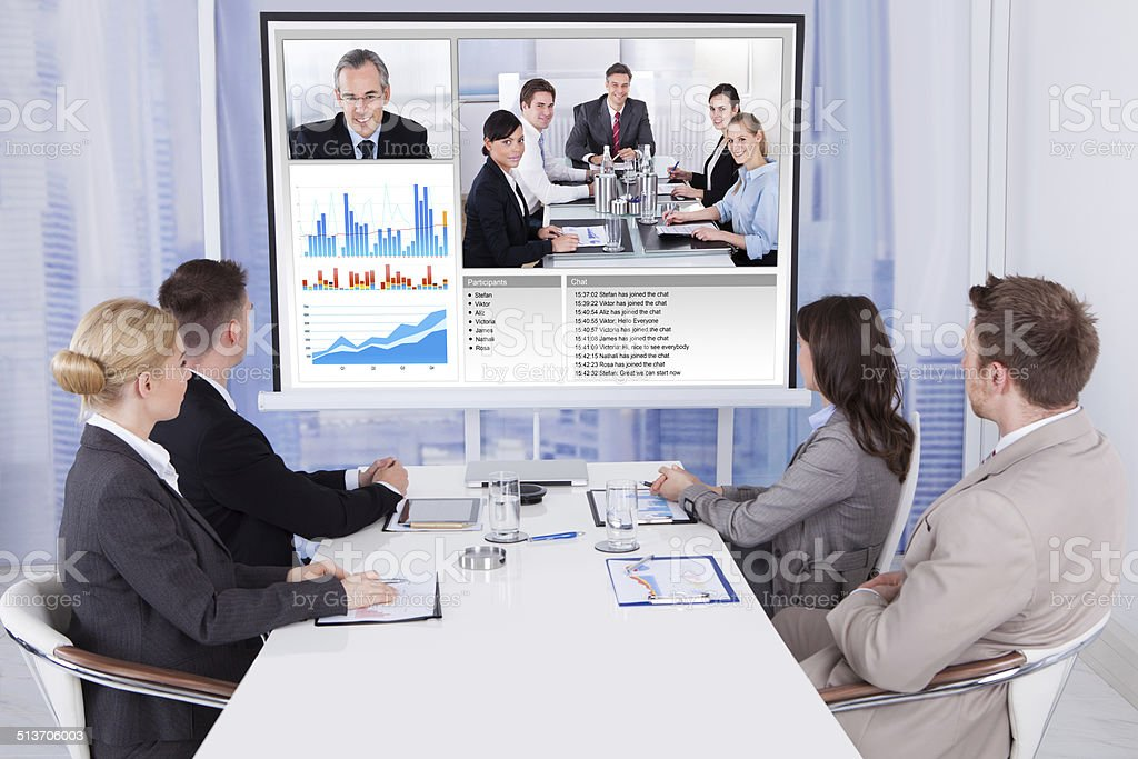Business People In Video Conference At Table stock photo
