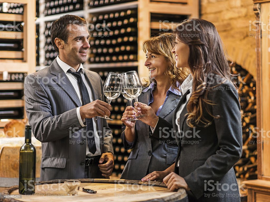 Business people in wine cellar. stock photo