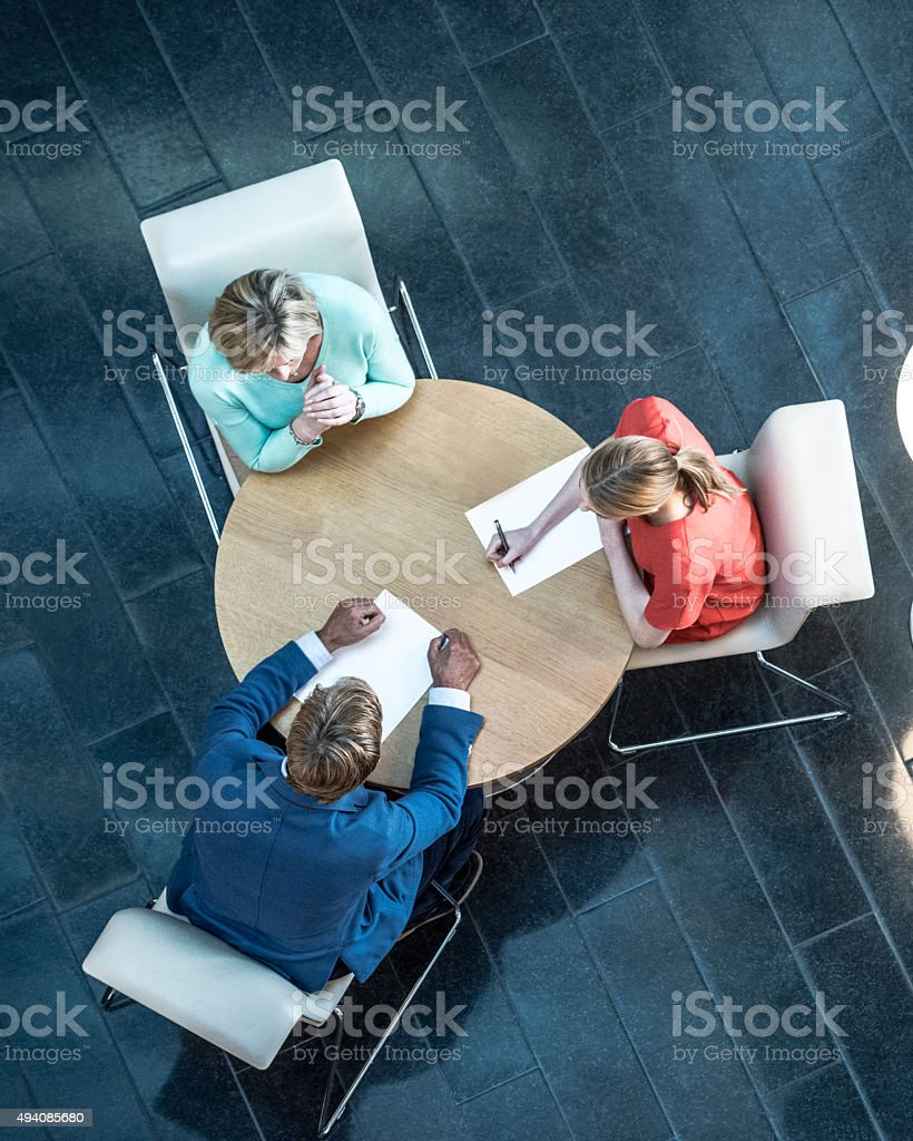 Business people in work meeting, overhead view stock photo