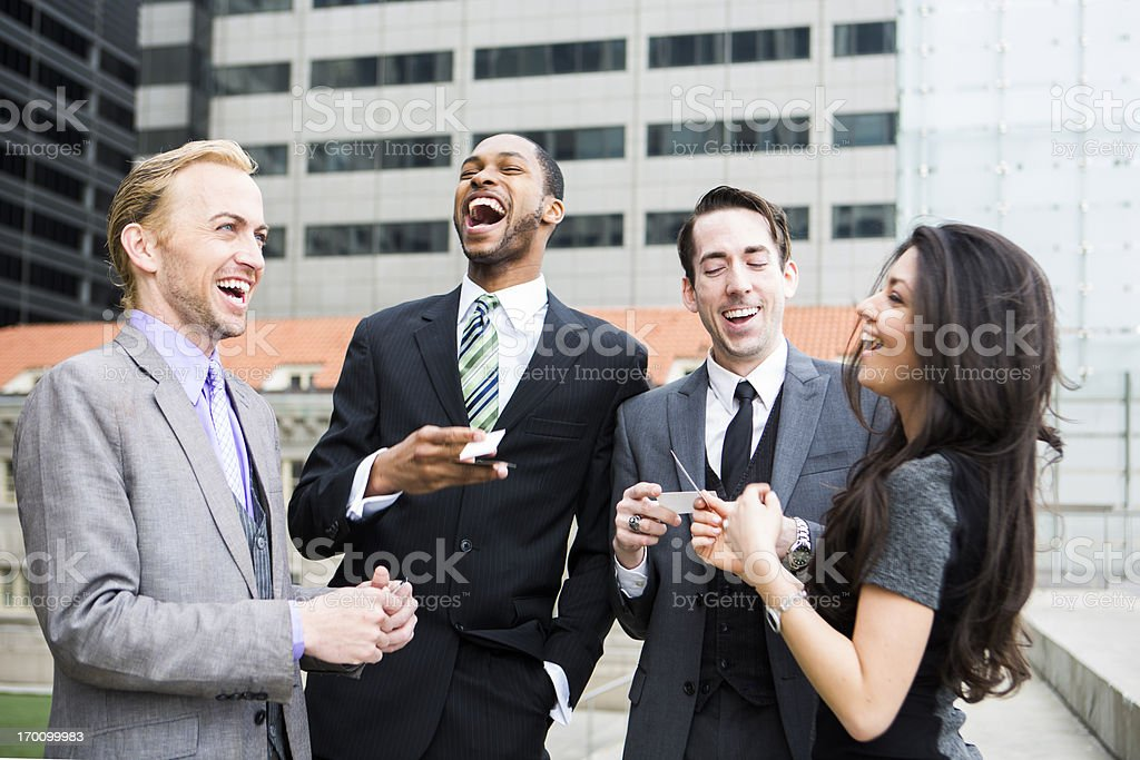 A group of business people exchanging cards and sharing a laugh