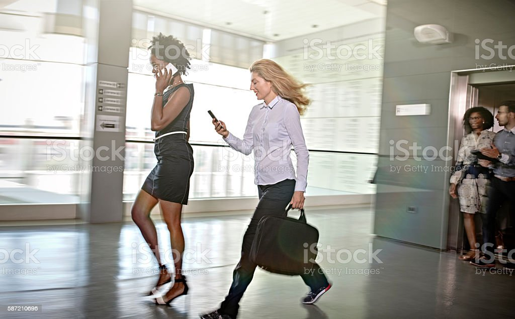 Business people leaving elevator stock photo
