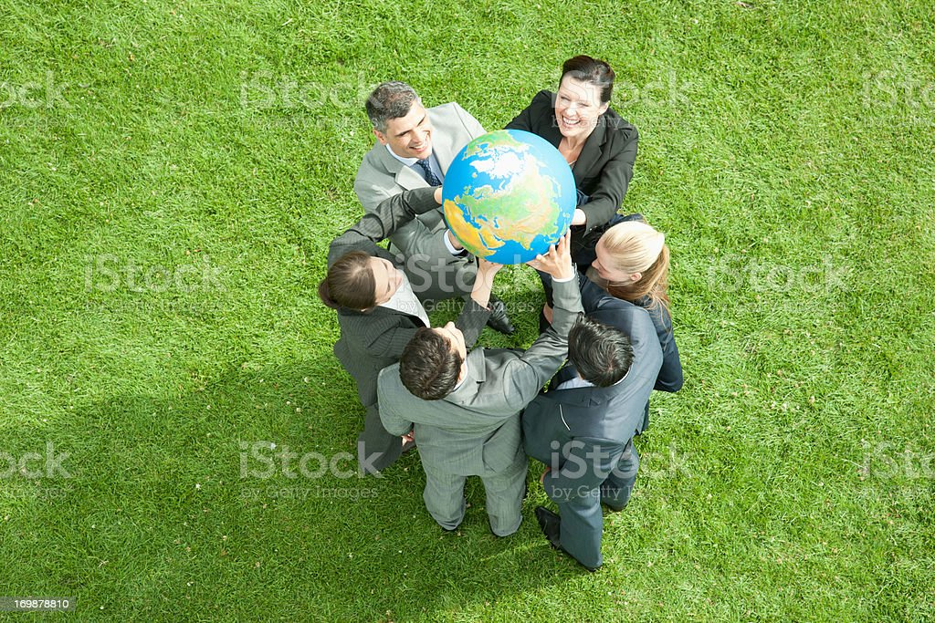 Business people lifting globe together outdoors stock photo