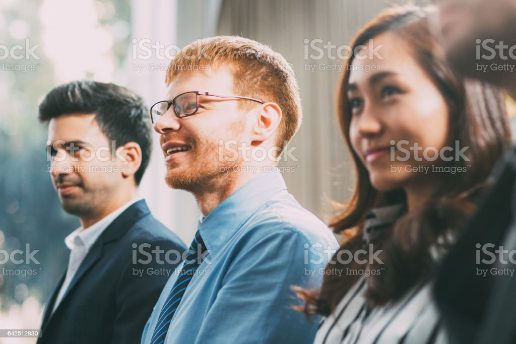 Business people listening to speaker and smiling stock photo