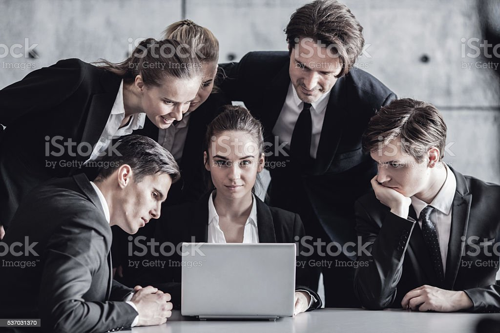 Business people look at laptop stock photo