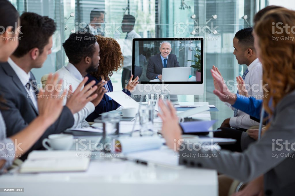 Business people looking at a screen during a video conference stock photo