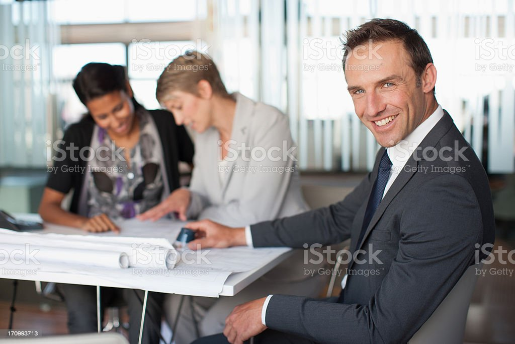 Business people looking at blueprints together stock photo