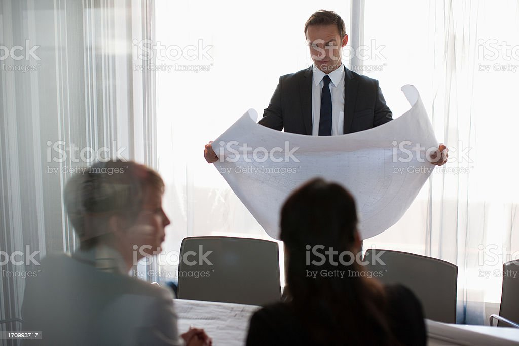 Business people looking at blueprints together royalty-free stock photo