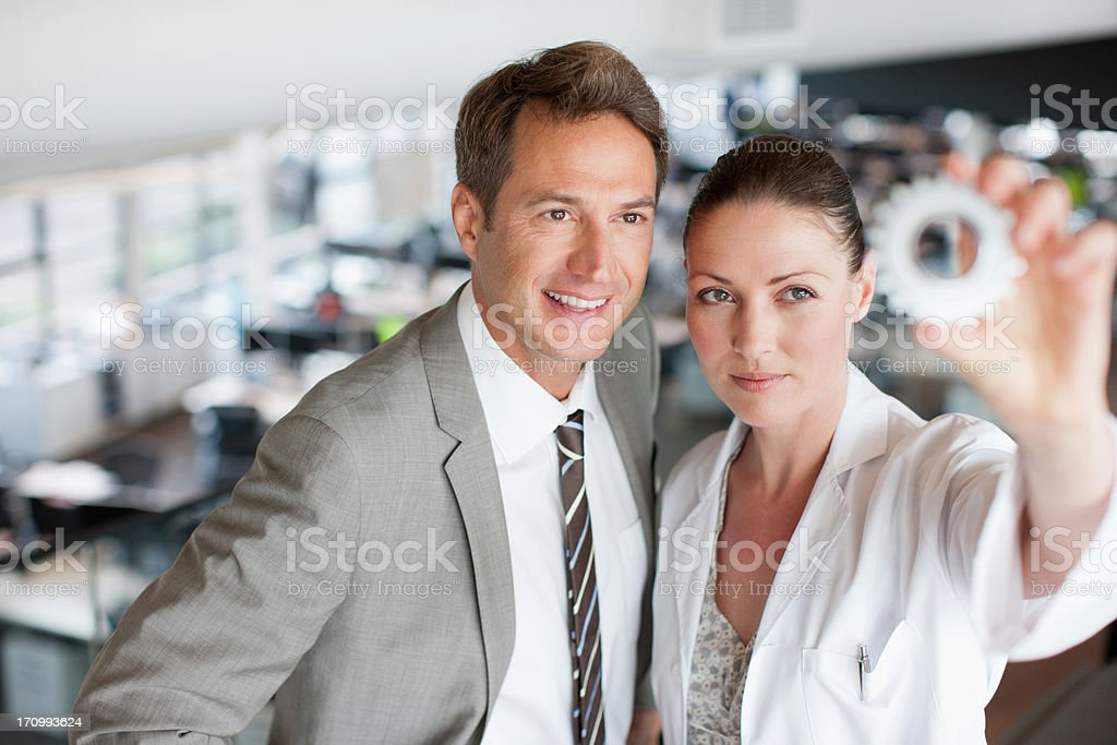 Business people looking at cog stock photo