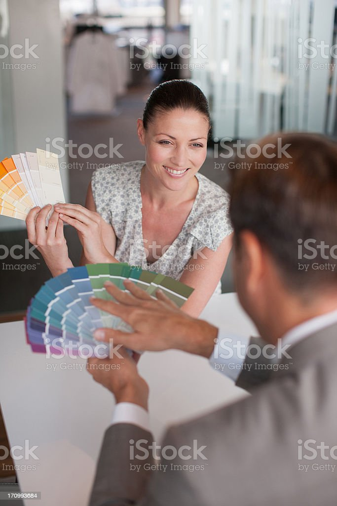 Business people looking at color swatches together stock photo