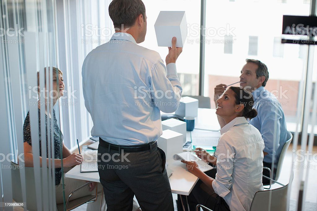 Business people looking at cubes in conference room stock photo