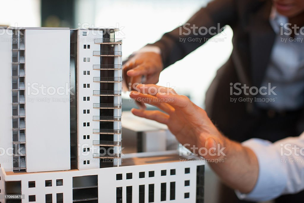 Business people looking at model building stock photo