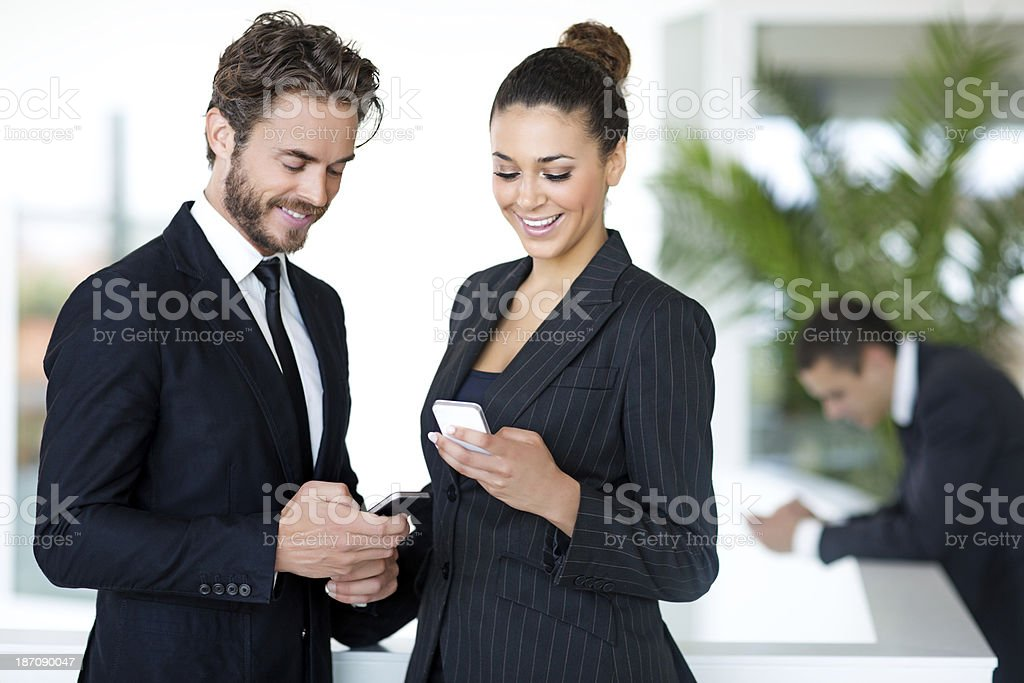 business people looking at phones in their hands stock photo
