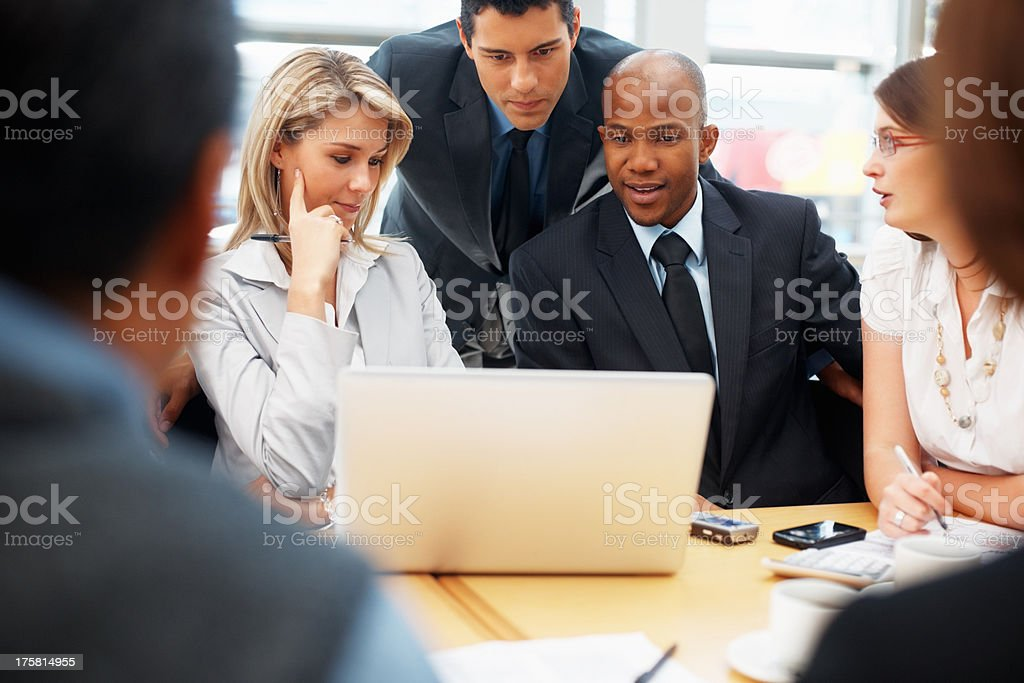 Business people looking at proposal on laptop stock photo