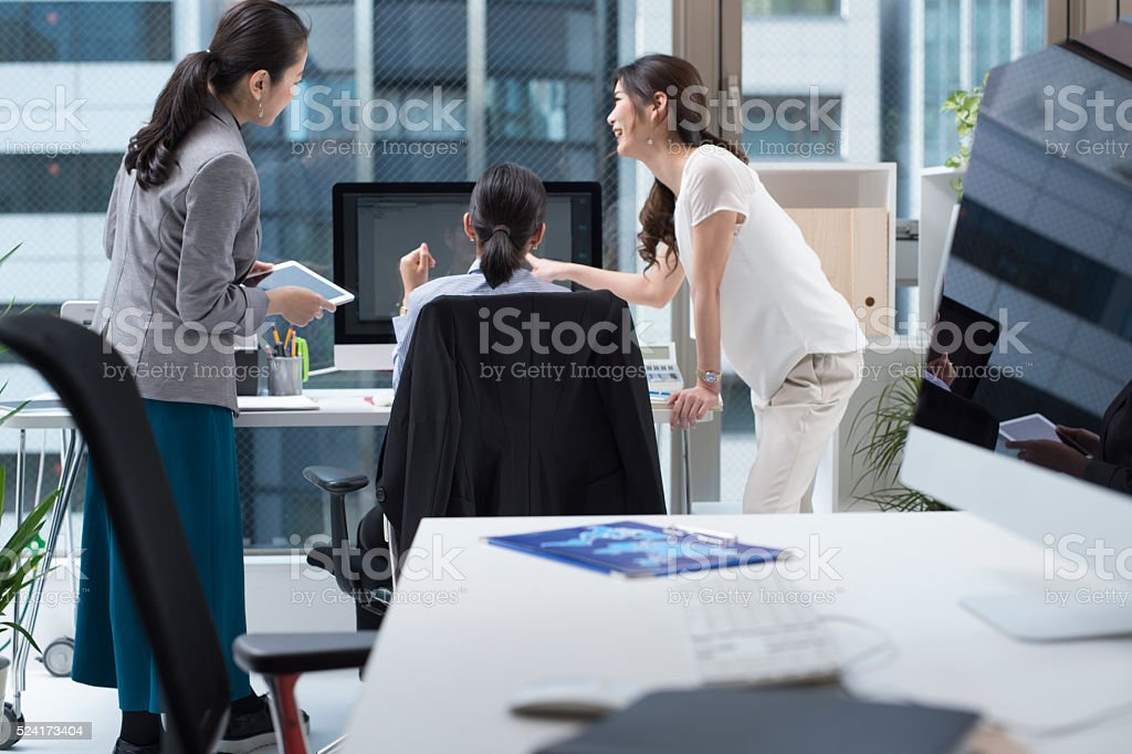 Business people looking at the computer\'s documentation