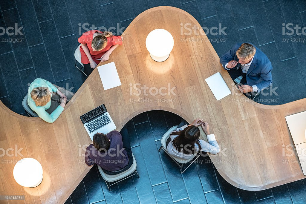 Business people meeting in modern office, view from above. stock photo