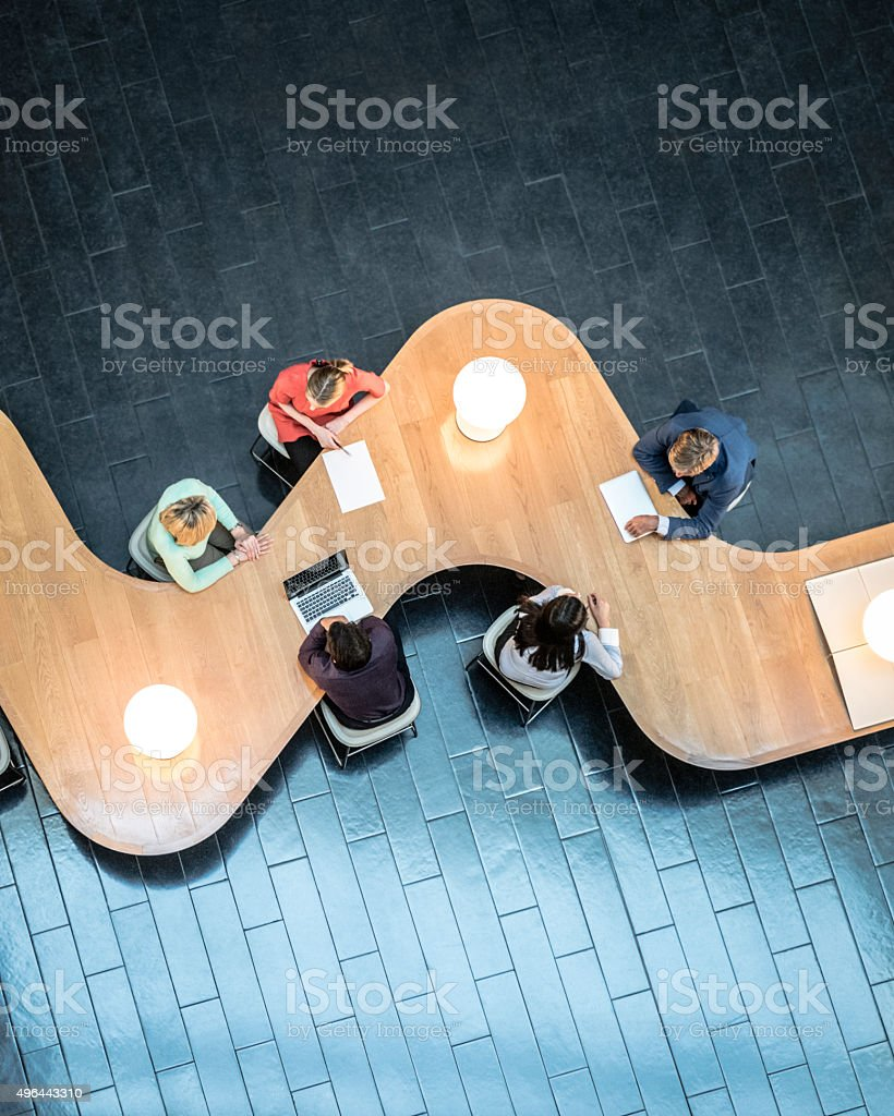 Office workers sitting at curved desk in business meeting....