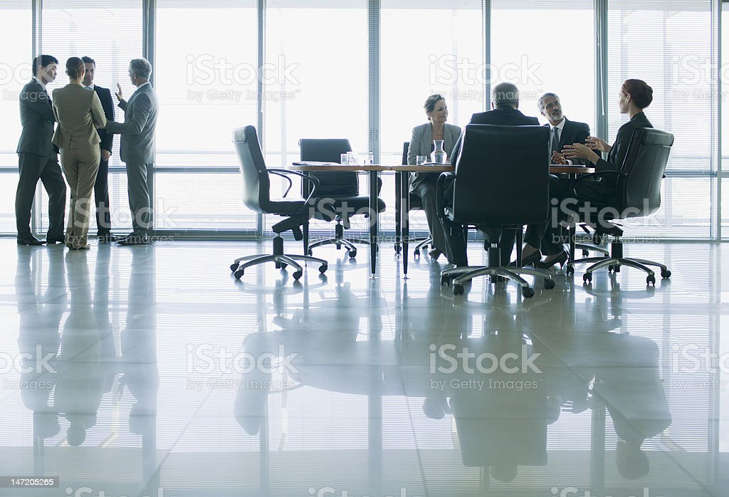 Business people meeting in separate groups in conference room stock photo