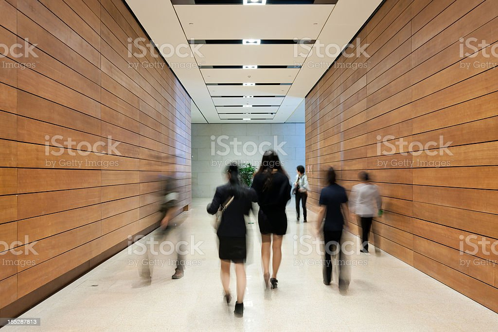 Business people moving along the corridor royalty-free stock photo