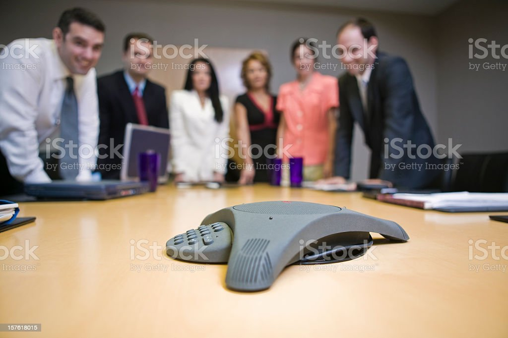 Business people on conference call around phone and table stock photo