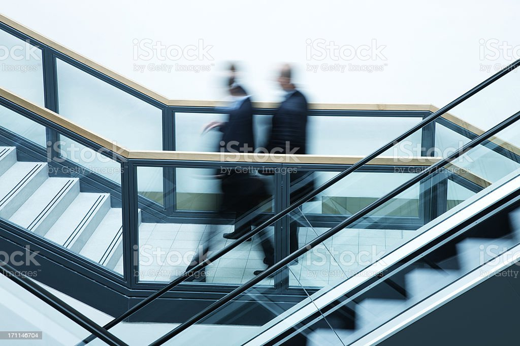 Business people on escalators, blurred motion royalty-free stock photo