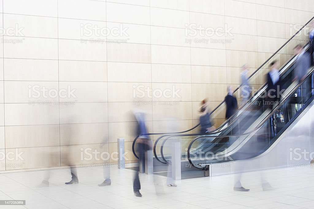 Business people on escalators stock photo
