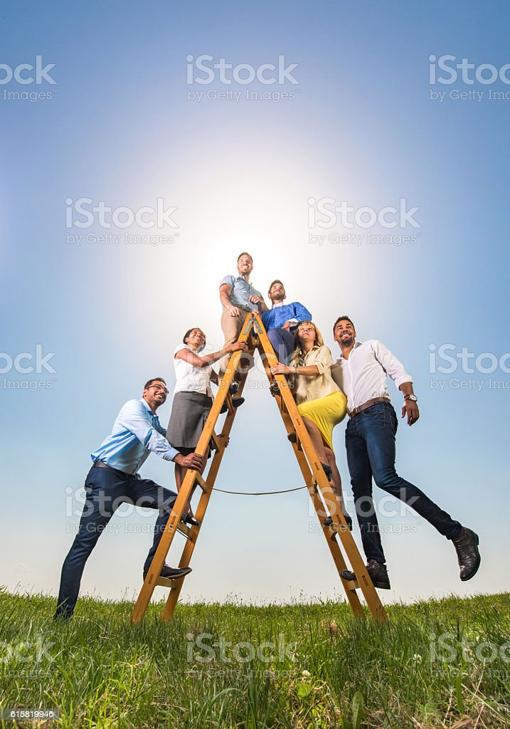 Business people on ladders of success against the sky. stock photo
